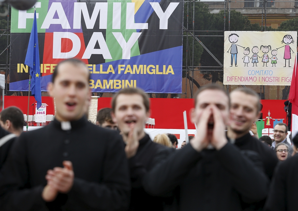 Priests shout slogans during a rally against same-sex unions and gay adoption in Rome, Italy January 30, 2016. Tens of thousands of Italians staged a mass rally in Rome's Circus Maximus on Saturday to urge the government to drop legislation that offers homosexual couples legal recognition and limited adoption rights. REUTERS/Remo Casilli - RTX24OGO